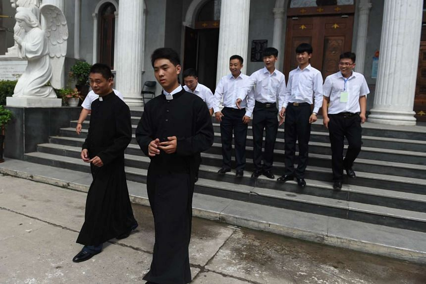 Catholic monks walk at the Sacred Heart of Jesus Catholic church, where Father Joseph Zhang Yilin was ordained as a bishop on August 4, 2015.