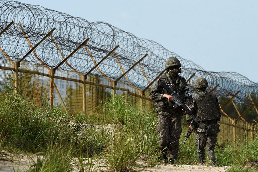 South Korean soldiers patrolling the scene of the blast at the demilitarised border with North Korea.