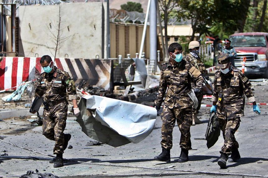 Members of the Afghan security services carry wreckage from the site of a suicide attack targeting the Kabul international airport, Afghanistan on Monday. At least five people, including the bomber, were killed and 18 injured 10 when the attacker det
