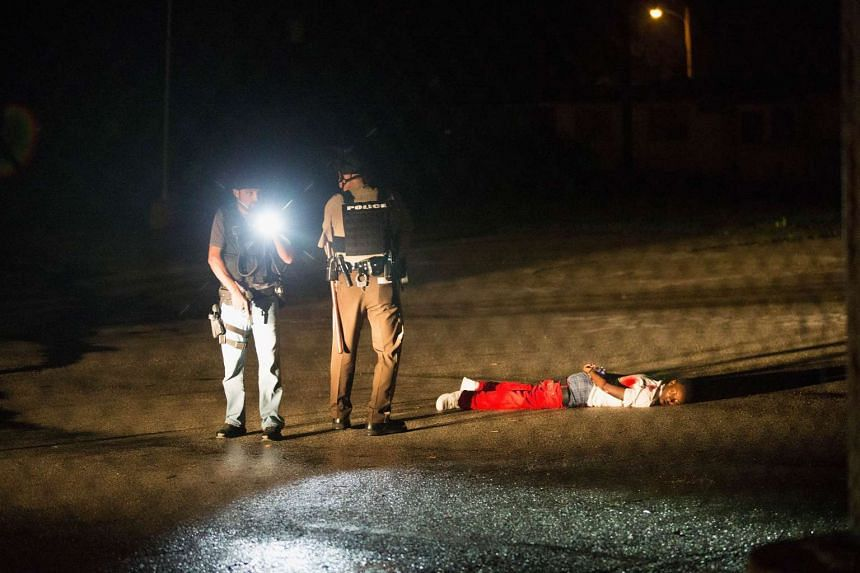 Police stand over a man with gunshot wounds lying in a parking lot after a shoot out with police along West Florissant Street during a demonstration to mark the one-year anniversary of the shooting of Michael Brown on Sunday in Ferguson, Missouri. Th