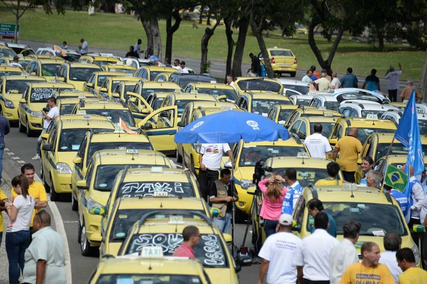 Hundreds of taxi drivers from Rio de Janeiro, Sao Paulo and Belo Horizonte block the avenue which links South and Center Rio de Janeiro on July 24, 2015, to protest against UBER, a mobile phone application to hail taxi.