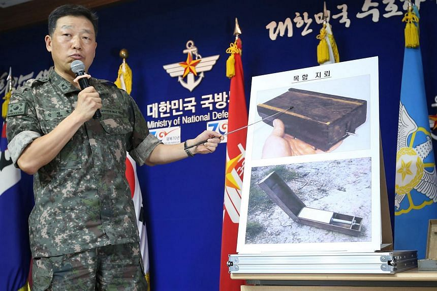"""A South Korean military officer shows pictures of North Korean """"wooden box"""" land mines during a briefing at the Defence Ministry in Seoul on Aug 10, 2015."""