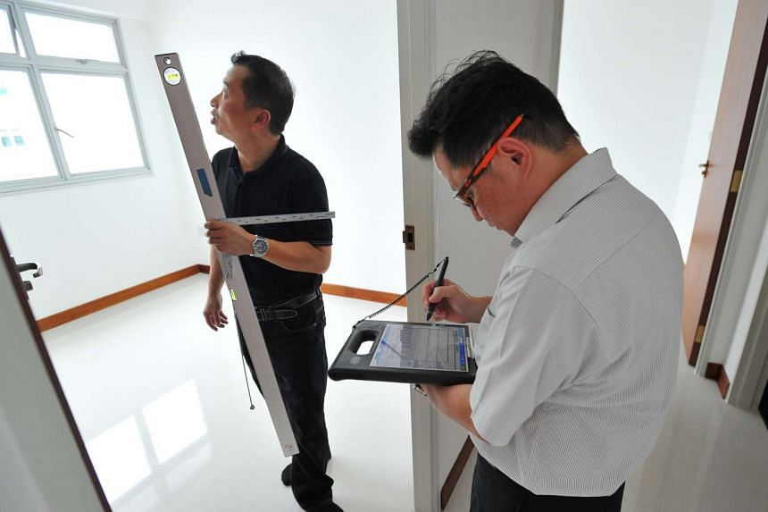 BCA assessors John Koh (left) and Simon Yee in a flat with their tools, which include a tablet, spirit level, 3mm thick plastic and paper gauge.