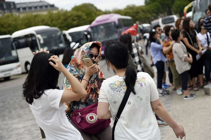 Chinese tourists wait for their bus after visiting the Versailles palace (Chateau de Versailles), outside Paris. PHOTO: AFP