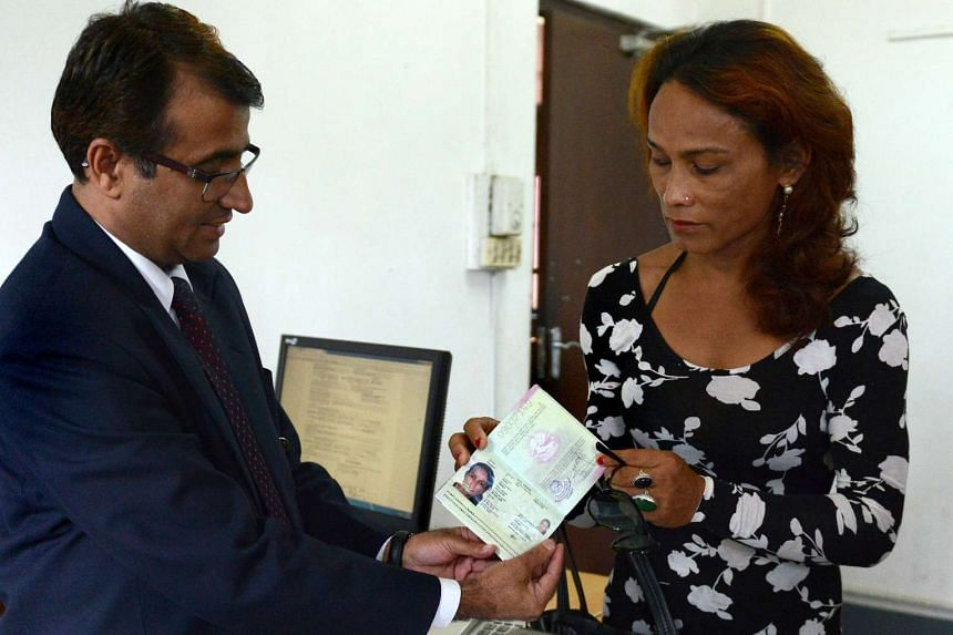 Nepalese transgender and the first recipient of a Nepalese transgender passport, Monica Shahi (right) from Kailali district receives her new passport at the offices of the passport department in Kathmandu on Aug 10, 2015.