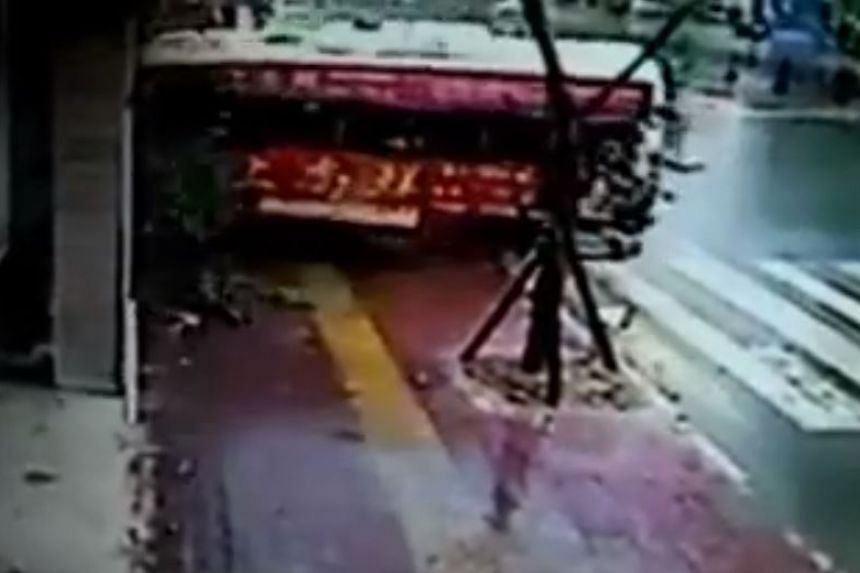 A bus sent hurtling down a street and into a building by winds from Typhoon Souledor.