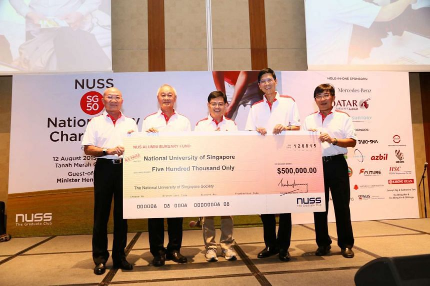 The National University of Singapore Society (NUSS) presenting a cheque for $500,000 to Education Minister Heng Swee Keat (centre) for the NUS Alumni Bursary Fund after raising the amount through a charity golf tournament.