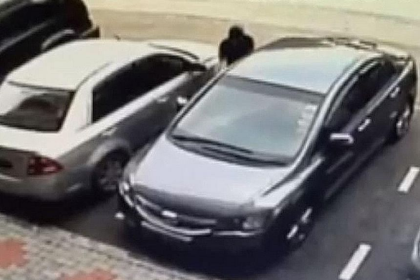 A CCTV video posted by Mr Khoo shows a white car stopping next to his grey car before a man gets out, unlocks the driver-side door of the six-year-old Honda Civic and drives it away.