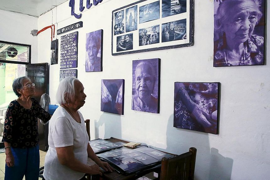 """Ms Estelita Dy (left) and Ms Hilaria Bustamante, who were """"comfort women"""" during World War II, looking at pictures of fellow survivors at a resource centre run by women's rights group Lila Pilipina in Quezon city, Manila, yesterday. The Filipino wome"""