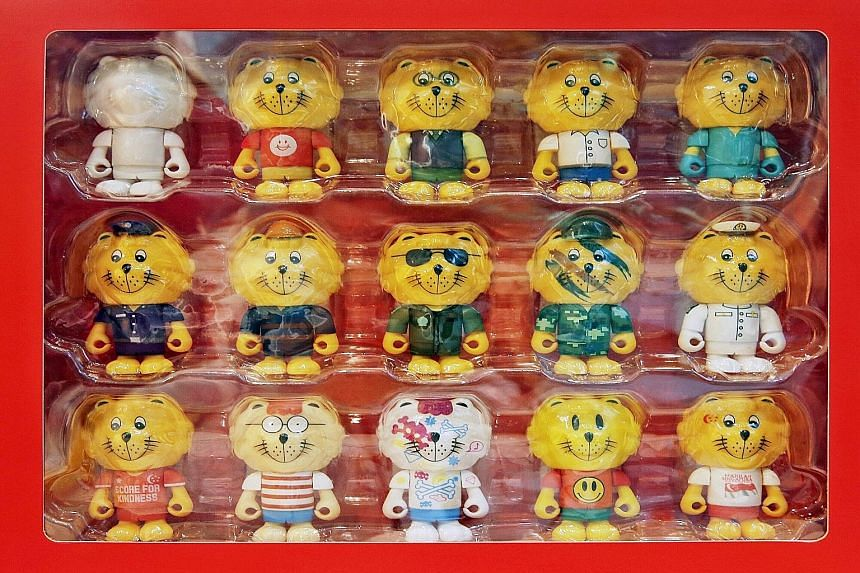 The queue for the Singa figurines at the Singapore Kindness Movement gallery. (Above) A set of 15 goes for $300, while individual Singas are sold at $10 each. The most popular Courtesy Lion is the NDP Singa (bottom right), which wears a white s