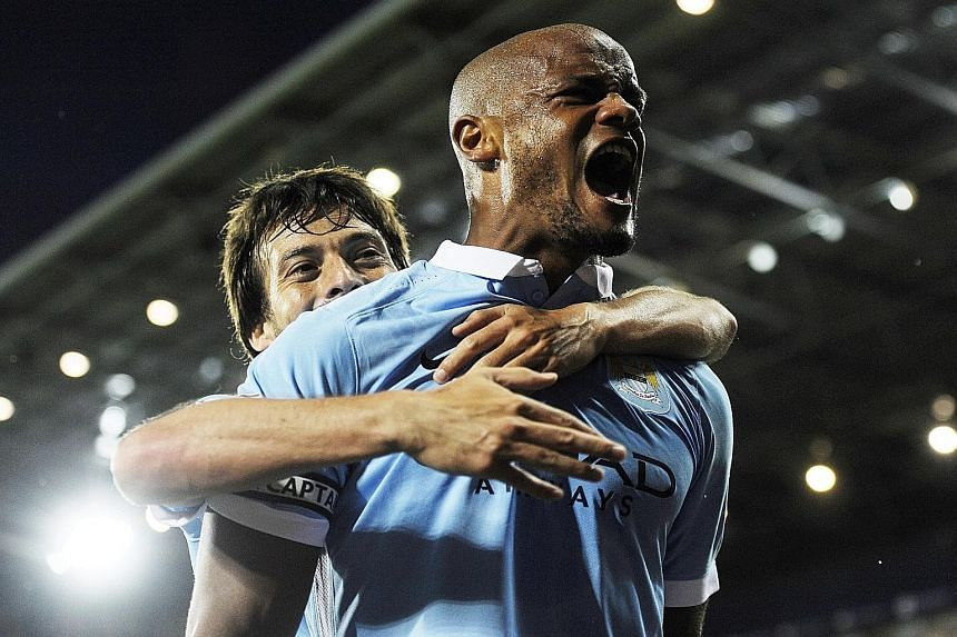 Manchester City's Vincent Kompany (right) celebrates with team-mate David Silva after scoring against West Bromwich Albion in the decisive 3-0 win on Monday.