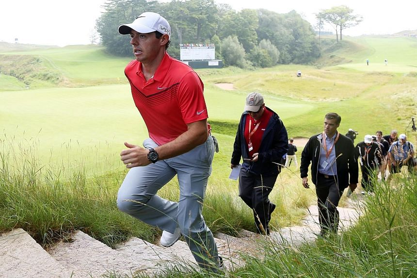 Defending champion Rory McIlroy, returning to competitive golf after more than seven weeks because of an ankle injury, shows no apparent ill-effects as he walks off the 18th green during a practice round for the US PGA Championship at Whistling Strai