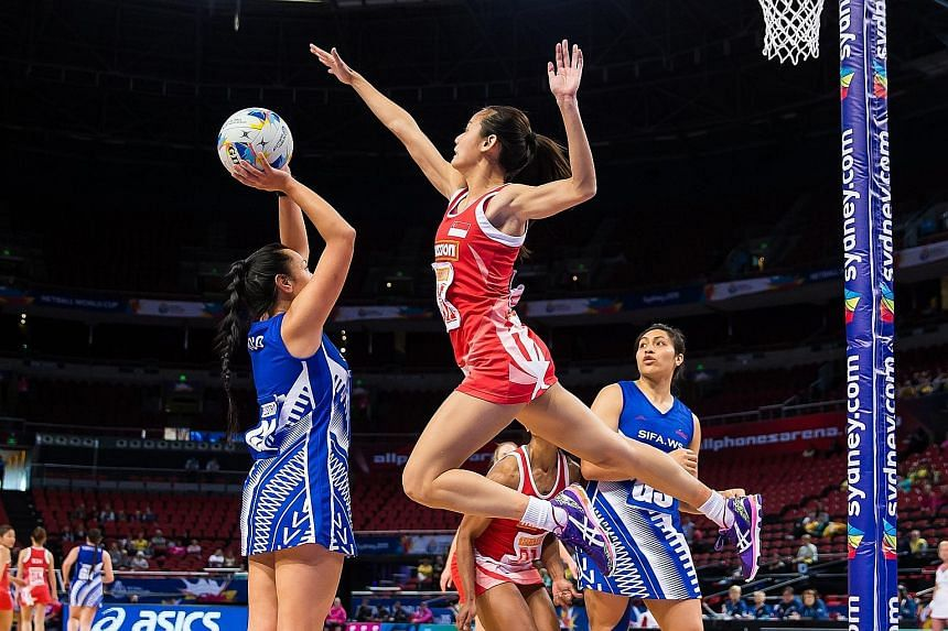 Singapore goalkeeper Micky Lin leaping to block Samoa's goal attack Julianna Naoupu, as goal shooter Auteletoa Tanimo readies for the rebound in their game, which the Pacific Islanders won 46-39.
