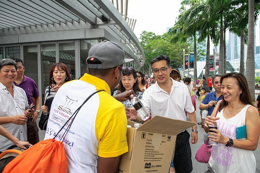 A Marina Bay Sands volunteer distributing bottled water to people lining up to visit the ArtScience Museum which offered free admission to its three exhibitions over the Golden Jubilee weekend.