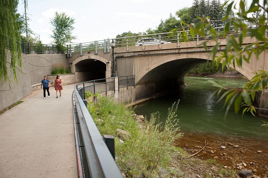 Two pedestrians who did not give their names walk by the Animas River on Aug 11, 2015 in Durango, Colorado.