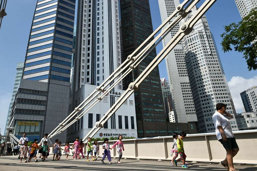 People walk across the Cavenagh bridge next to the financial district of Singapore on Aug 11, 2015.