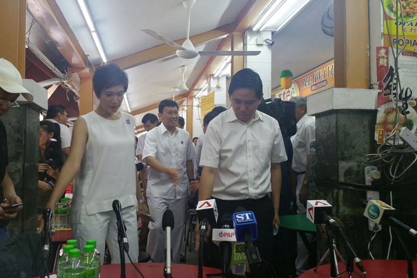 Mr Chee Hong Tat (centre) prepares to address the public during a PAP press conference at a coffeeshop in Toa Payoh central.