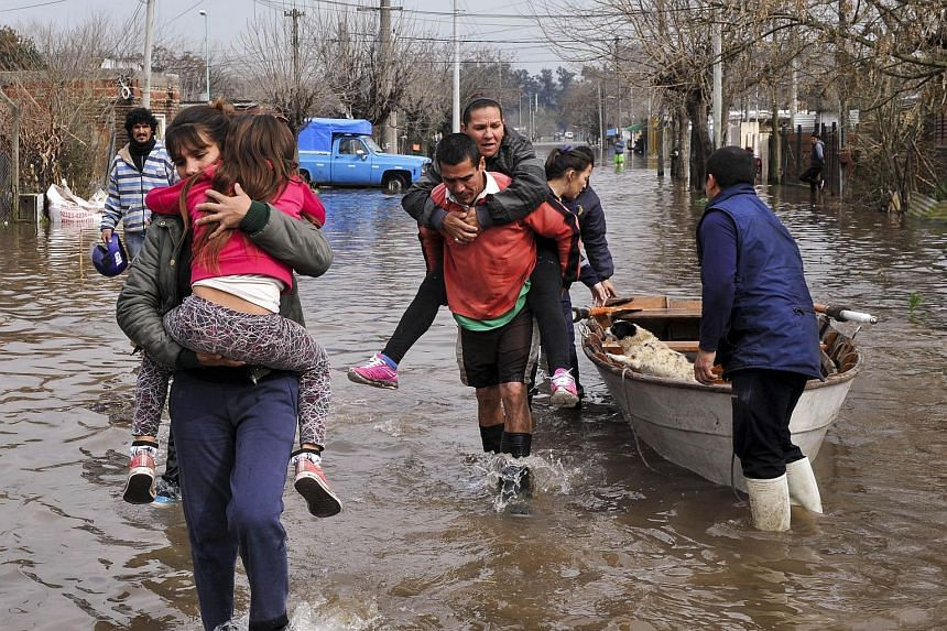 Residents evacuating a flooded area in Lujan, Buenos Aires province, Argentina on Aug 11, 2015.