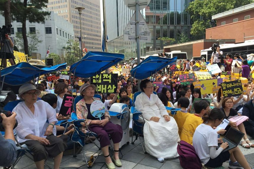 Three victims of military sexual slavery, euphemistically called comfort women, at a weekly protest in front of the Japanese Embassy in Seoul to demand an apology and compensation for their sufferings during World War II. On Wedneday, they were joine