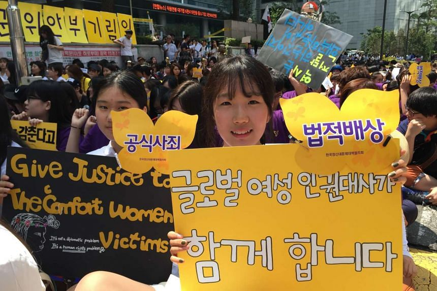 """Student Choi Go Eun, 16, holding up a yellow sign that says """"Global Female Rights Ambassadors are with you"""", is one of the more than 1,000 people who on Wednesday turned up at the weekly protest held in front of the Japanese Embassy in Seoul to deman"""
