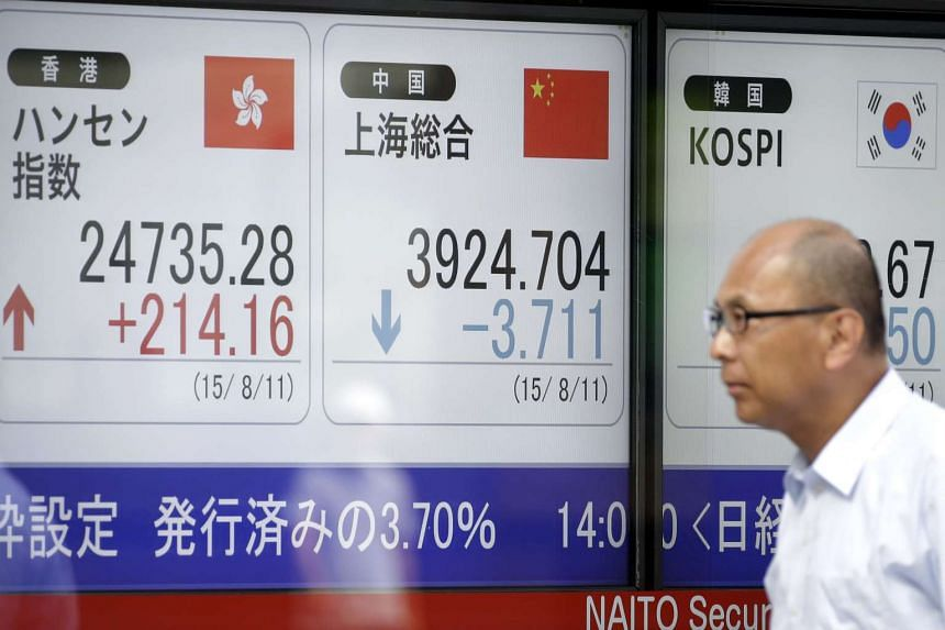 A pedestrian walks past an electronic stock board displaying the Hang Seng Index (left), the Shanghai Composite Index (center) and the Kospi index outside a securities firm in Tokyo, Japan on Aug 11, 2015.