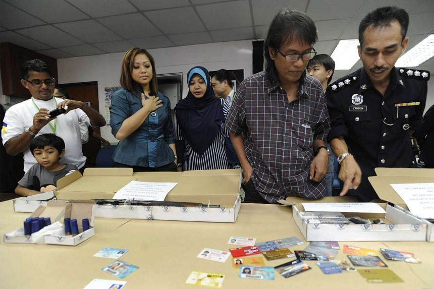 Singaporean victim Affandi Mahat (second from right, in checkered shirt) looking at the recovered items put on display at the Johor police headquarters on July 7, 2012.