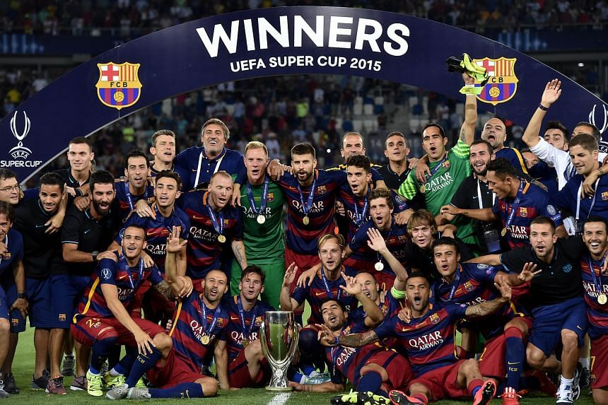 Barcelona's team celebrates with the trophy after winning the Uefa Super Cup final football match between FC Barcelona and Sevilla FC on Aug 11, 2015 at the Boris Paichadze Dinamo Arena in Tbilisi.