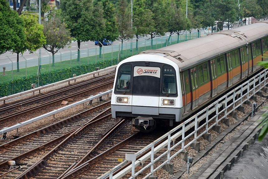 An MRT train travelling on the tracks along a station.
