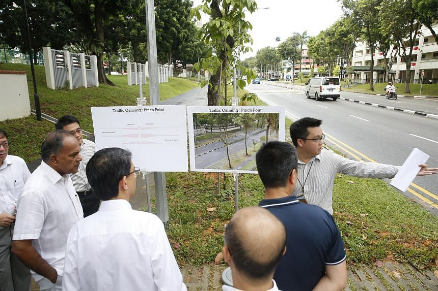 A Land Transport Authority road safety engineer (right) shows Law Minister K Shanmugam and Parliamentary Secretary for Health and Transport Assoc Prof Muhammad Faishal Ibrahim the location along Yishun Ring Road's Silver Zone site, where a pinch poin