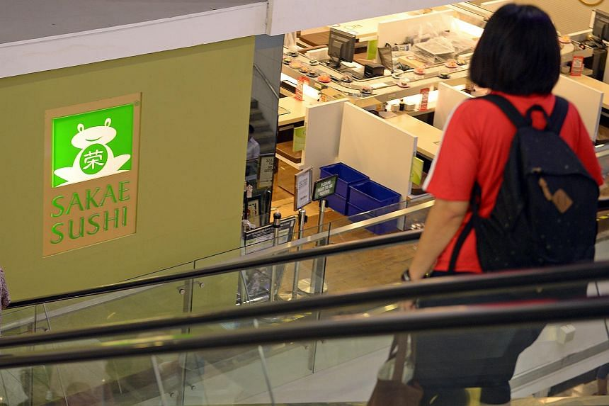 People going down the escalator near the Sakae Sushi outlet in Square 2.