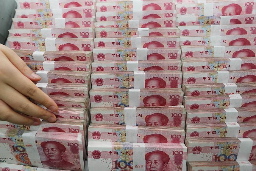 A teller counts yuan banknotes in a bank in Lianyungang, east China's Jiangsu province on Aug 11, 2015.