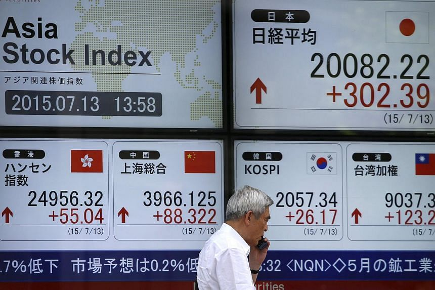 A man walks past in front of an electronic board displaying various Asian countries' stock price index outside a brokerage in Tokyo.
