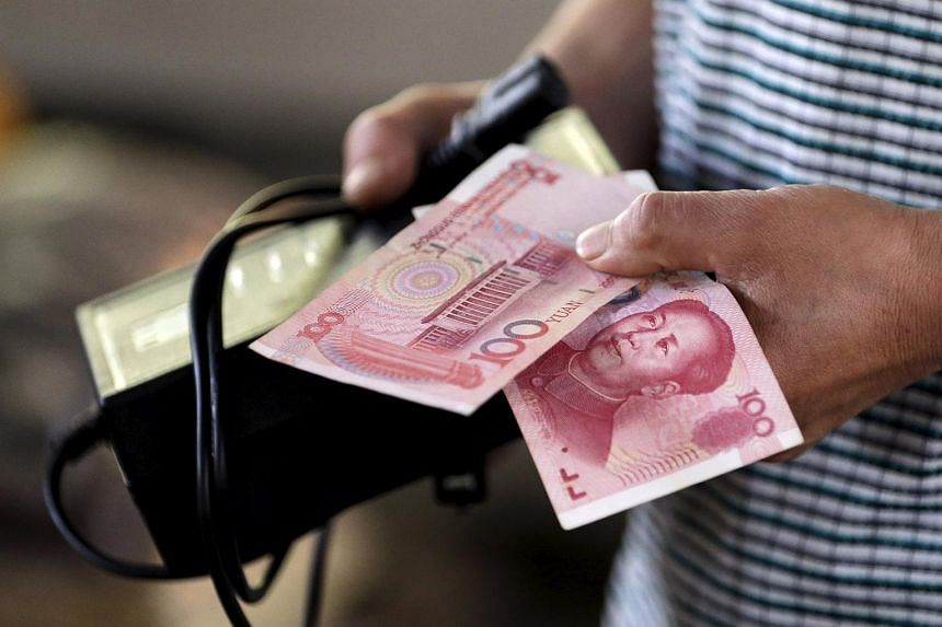 A customer holds a 100 Yuan note at a market in Beijing, on Aug 12, 2015.