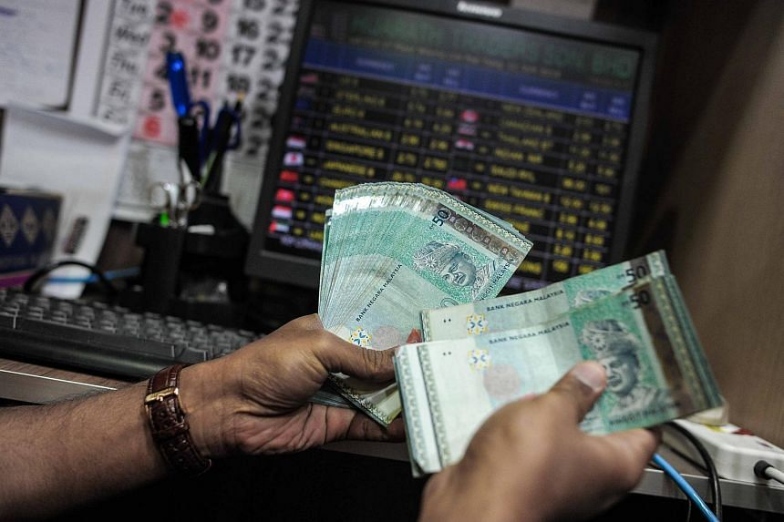 A money changer counts Malaysian ringgit banknotes for customers in Kuala Lumpur on June 11, 2015.