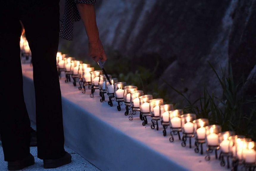 Relatives of Japan Airlines crash victims light candles during the memorial ceremony in Ueno village, Gunma prefecture on Aug 12, 2015.
