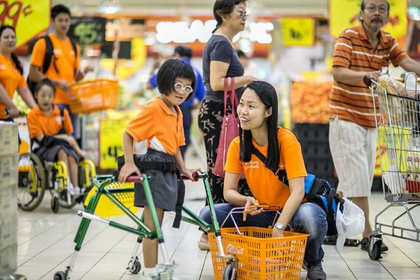 """Staff from Sembcorp Industries, like Wendy Khoo (right), took 30 students from the Cerebral Palsy Alliance Singapore School, including Nur Andreanna Ashmoori (left),  to the supermarket and gave them cash vouchers as part of """"Sembcorp Gives Back Day"""""""