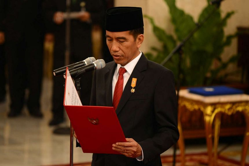 Indonesian President Joko Widodo swears into office the six newly appointed ministers during official ceremony at the presidential palace in Jakarta on Aug 12, 2015.
