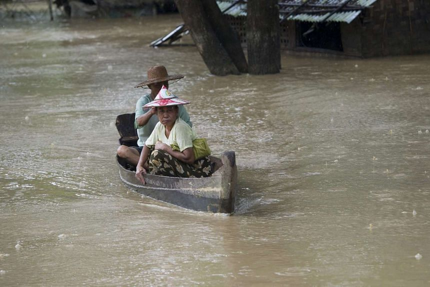 Local residents travel by boat past houses submerged by floodwaters in the town of Hinthada in Myanmar's Irrawaddy region on Aug 10, 2015.