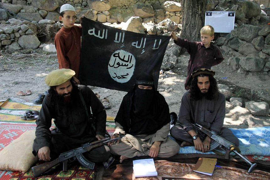 Gul Dali (right) the district leader of Islamic State in Iraq and Syria (ISIS), sitting with colleagues and his family at an undisclosed location in Kunar province, Afghanistan, on July 30, 2015.