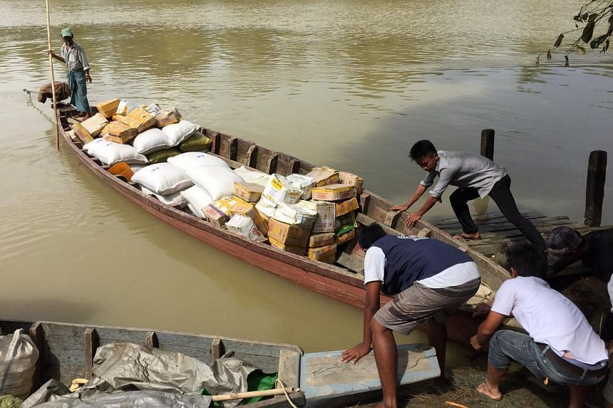 Mercy Relief personnel traveling by boat to deliver supplies to Kha Maung Taw Village.