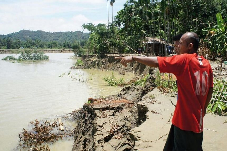 U Khin Thein, 42, pointing to where the river bank used to be.