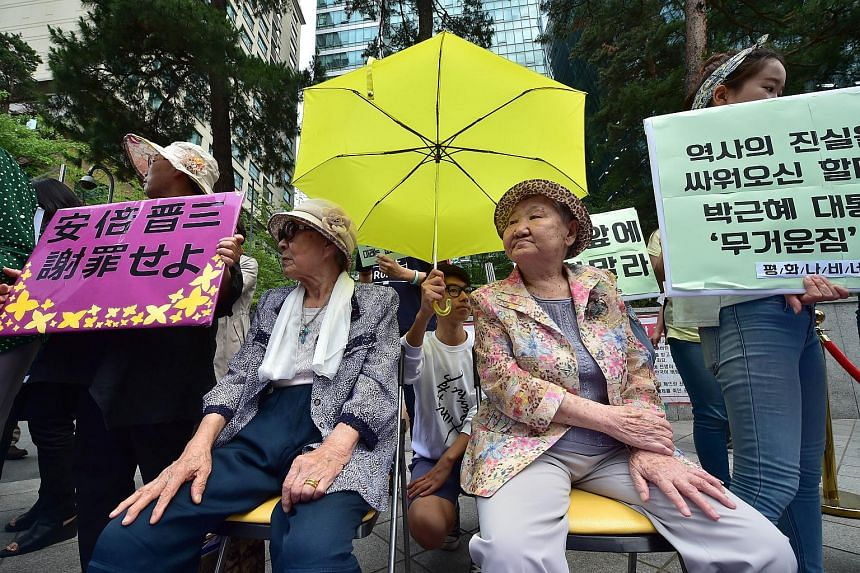 "South Korean former ""comfort women"" Kim Bok-Dong (left) and Gil Won-Ok, who were forced to serve as sex slaves for Japanese troops during World War II, sit under a yellow umbrella during a press conference outside the Japanese embassy in Seoul."