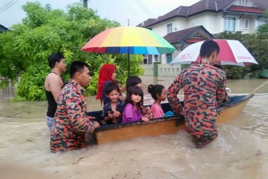 Bestari Jaya fire and rescue officers taking children from a kindergarten in Puncak Alam to safety on a boat after 20 of them were trapped during flash floods.
