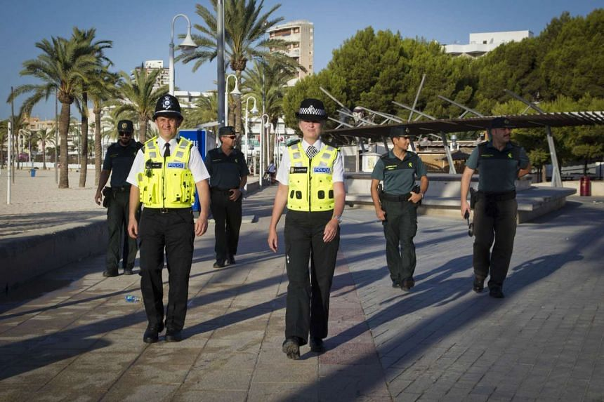 """British police officers, popularly known as """"bobbies"""" walk Spanish Civil Guards Tuesday as they patrol at Punta Ballena street in the holiday resort of Magaluf in Calvia on Majorca Island, where the British holidaymakers' alcohol and sex excesses"""