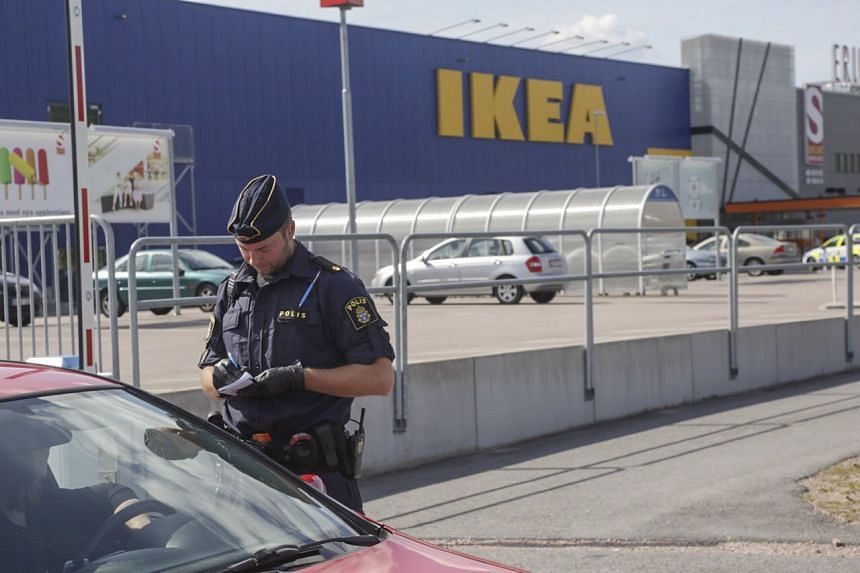 A police officer writes on a notepad as he speaks to a driver near the Ikea store where two people died in a knife attack in Vasteras, central Sweden on Monday.