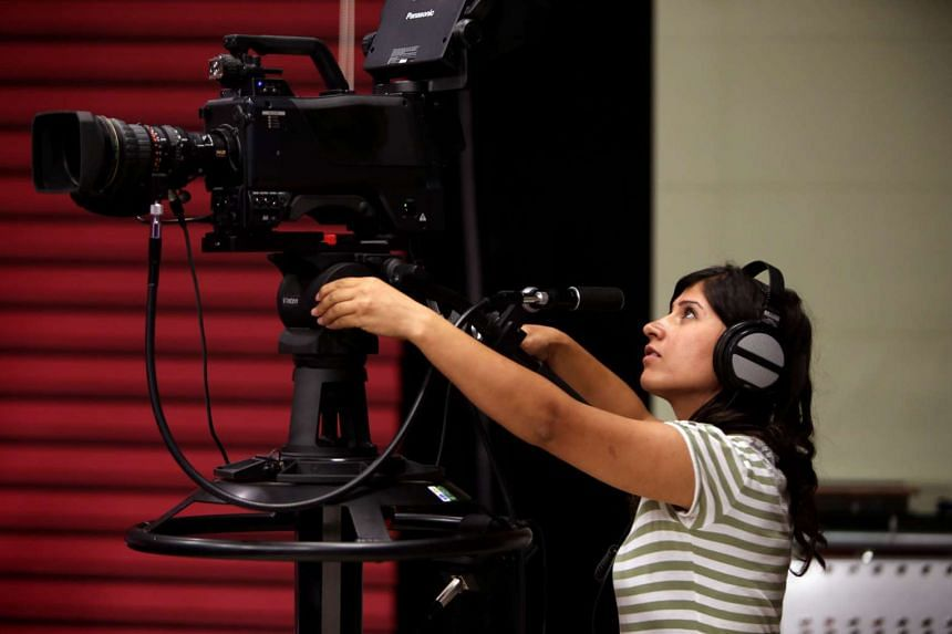 A camerawoman from Ronahi TV, the only Syrian satellite channel that broadcasts in Kurdish, works at the studio in Qamishli, a Kurdish-majority city in Syria's northeastern Hasakeh province, on July 14.