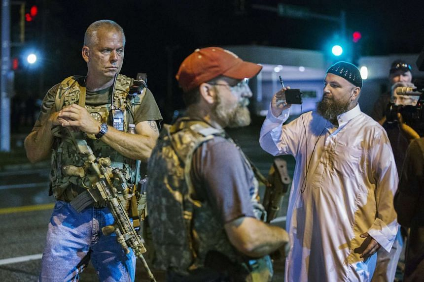 Members of the Oath Keepers walk with their personal weapons on the street during protests in Ferguson, Missouri on Tuesday.