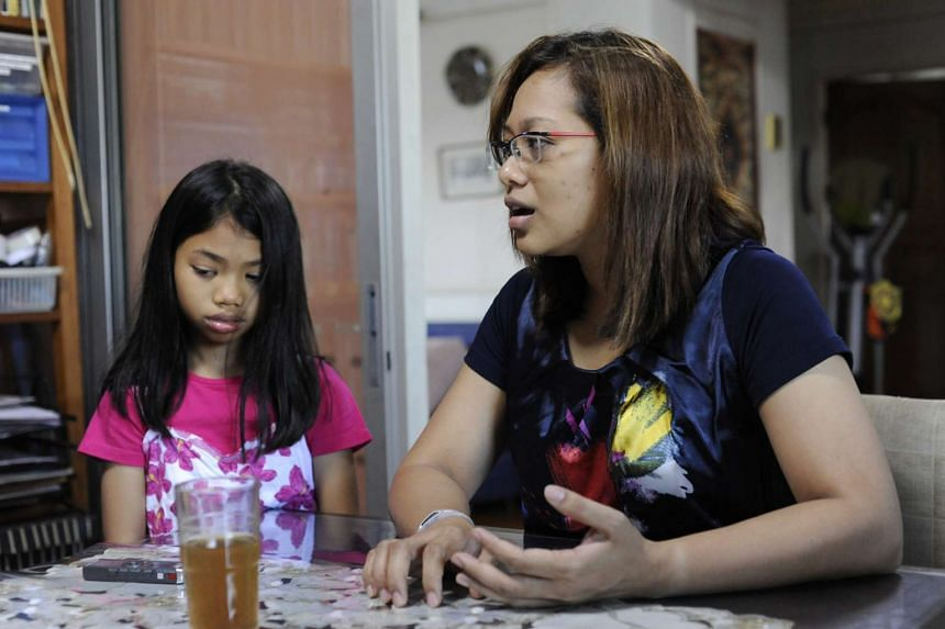 Madam Rita Zahara (right) with her daughter Sharifah Nadhrah, speaking to the reporter at home. PHOTO: ST FILE