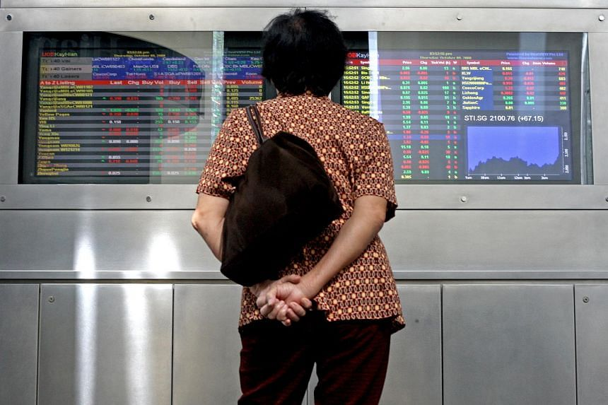 A lady watching the stock index at UOB Plaza.