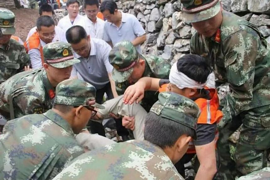 Rescuers carrying a victim after a landslide in Shanyang county, north China's Shaanxi province on Aug 12, 2015.